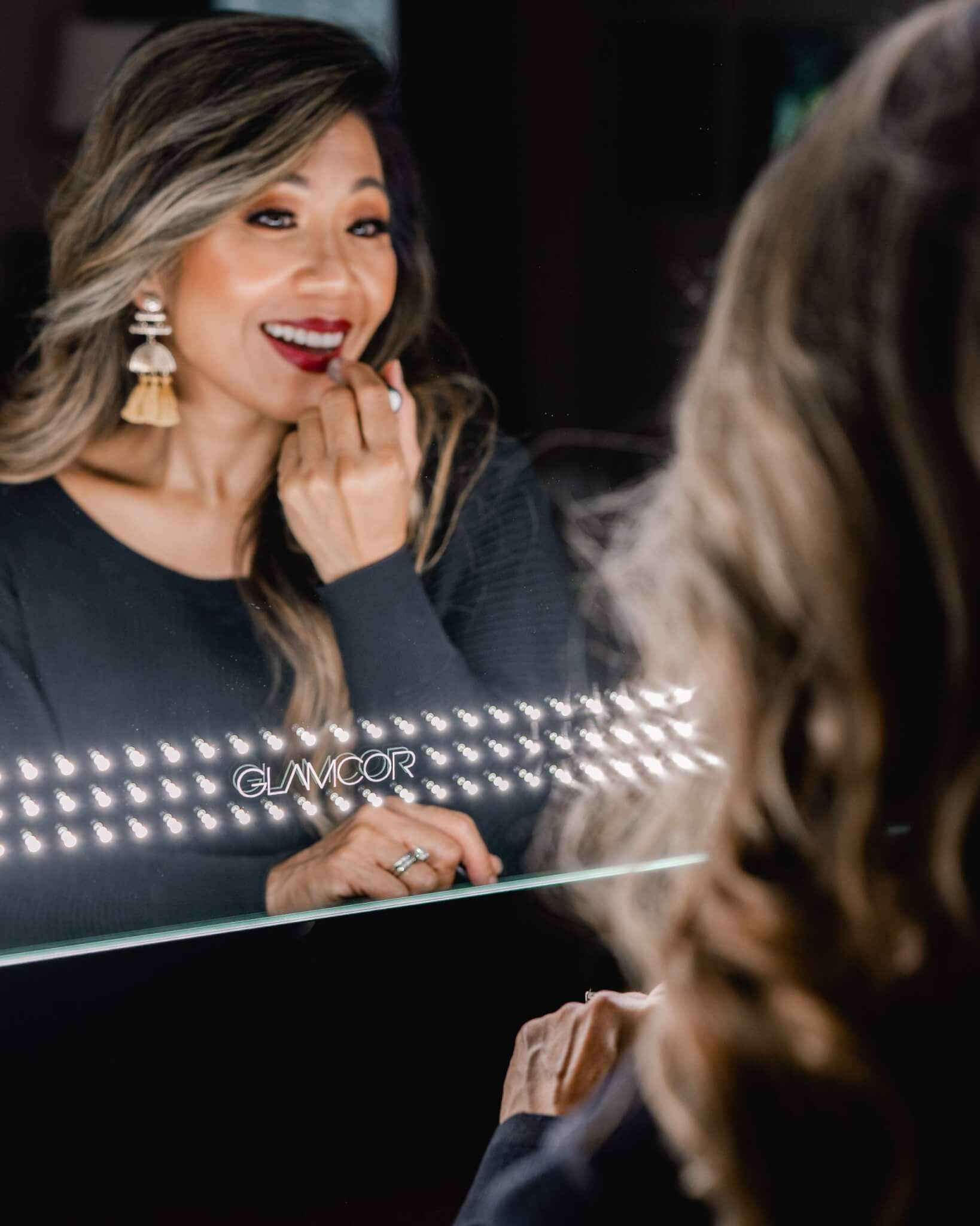 woman standing in front of glamcor socialite mirror smiling and applying red lipstick