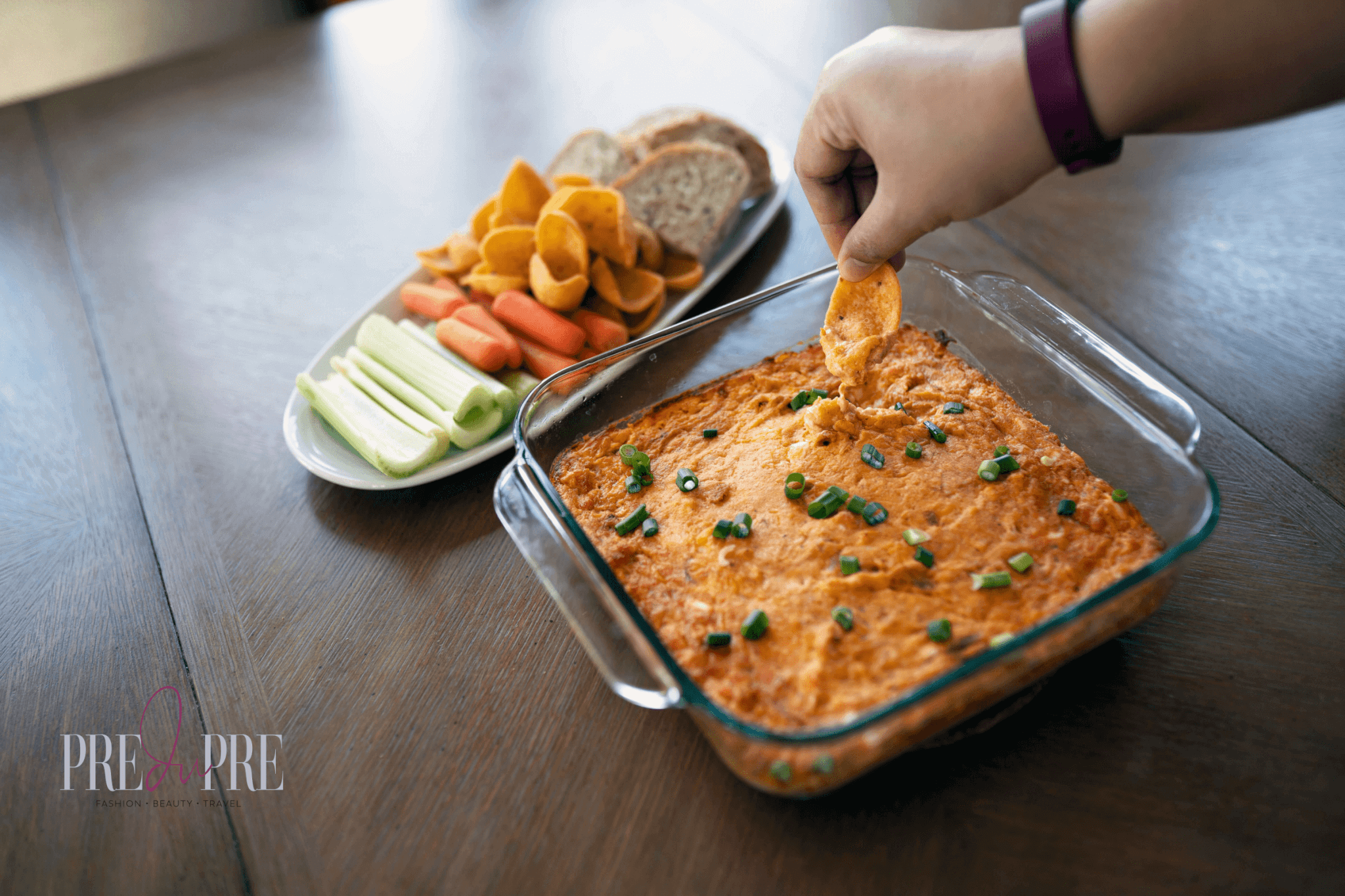 lady's hand with corn chip scoop dipping into chicken buffalo dip